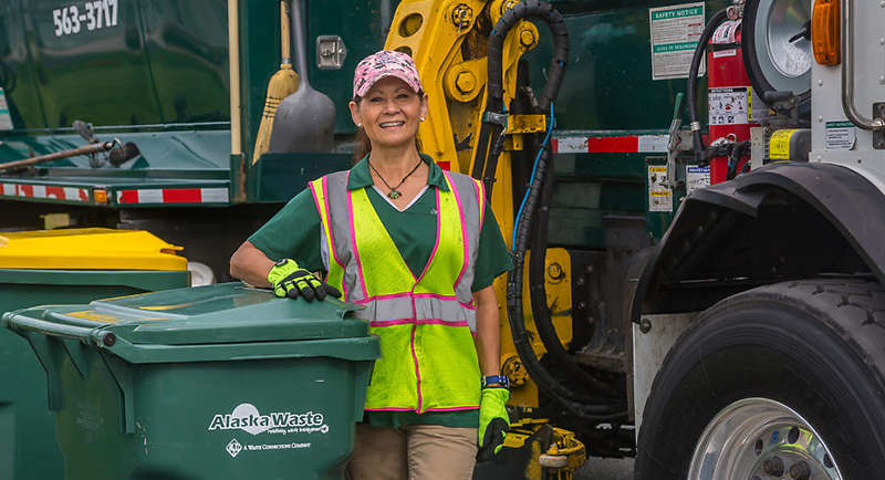 Photo of Alaska Waste employee standing between a truck and a bin.