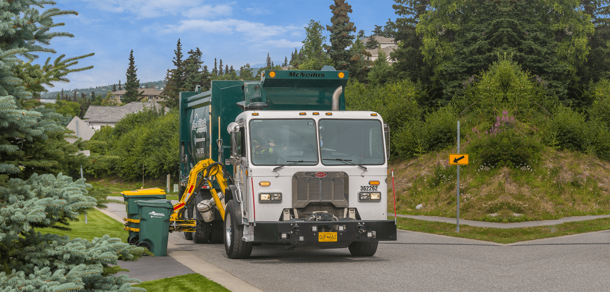 Photo of Alaska Waste truck servicing trash and recycling carts in a residential area.
