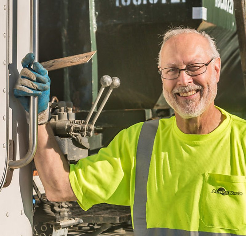 Alaska Waste Professional Driver smiling by his truck.